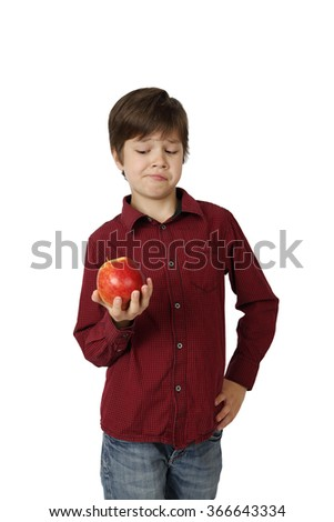 Teenage boy skeptically looks at apple in his hand isolated on white background - stock photo