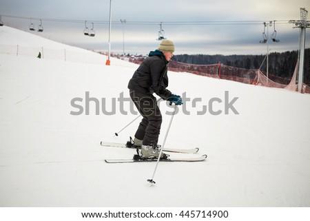 Teenage boy skis on snowy slope at ski resort. - stock photo