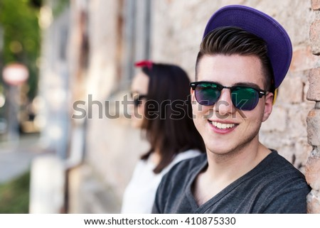 Teenage boy smiling at camera, wearing cap and sunglasses. Hipster, modern, real people. Depth of field, selective focus  - stock photo