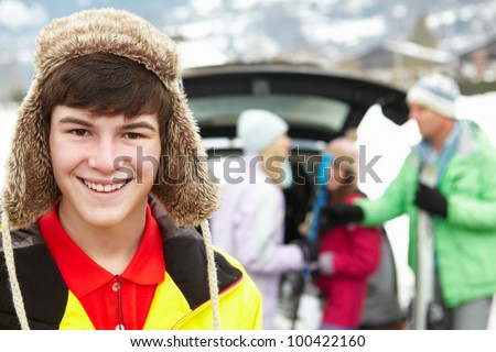 Teenage Boy Smiling At Camera Whilst Family Load Skis In Boot Of Car - stock photo