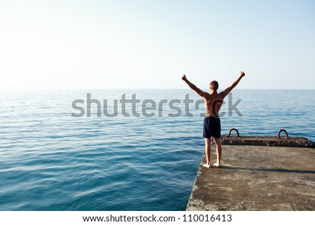 Teenage boy standing on pier against sea with hands up