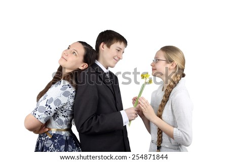 Teenage boy stands back to back with one girl and gives flowers to another isolated on white background - Inconstancy and volatility of youth concept - stock photo