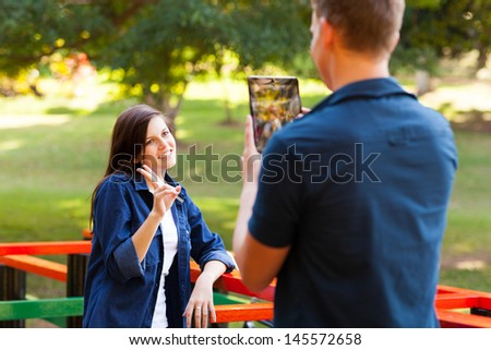 teenage boy taking picture of his girlfriend using tablet computer - stock photo