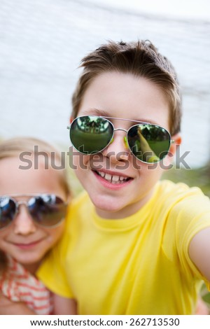 Teenage boy taking selfie with his little sister outdoors on summer day - stock photo
