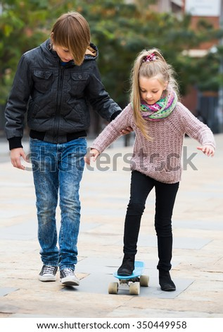 Teenage boy teaching younger sister skateboarding in fall day