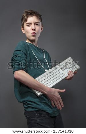 teenage boy using a computer keyboard like a guitar, isolated on gray - stock photo