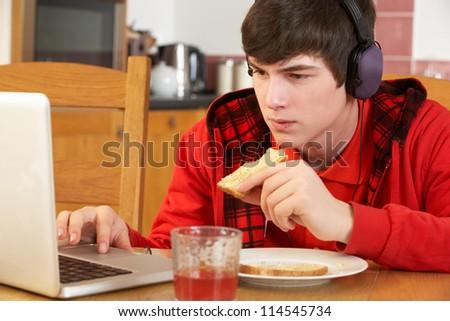 Teenage Boy Using Laptop Whilst Eating Breakfast - stock photo