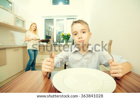 Teenage boy waiting for dinner and playing with forks while his mother cooking in the kitchen - stock photo