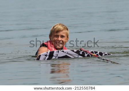 teenage boy waiting to get up on a wakeboard - stock photo