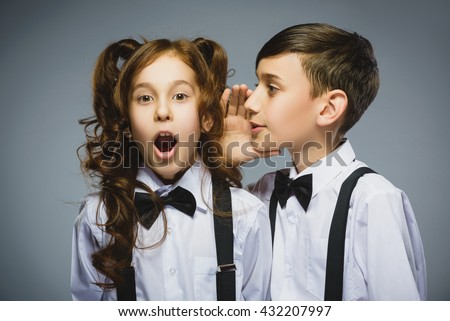 Teenage boy whispering in the ear of teen girl on a gray background. Positive human emotion, facial expression. Closeup. Communication concept