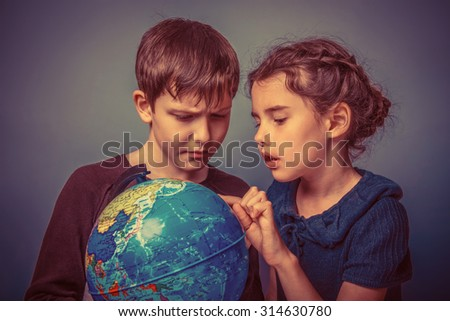 Teenage boy with a girl looking at a globe girl opened her mouth on a gray  background retro - stock photo