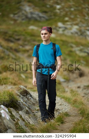 Teenage boy with backpack hiking on a mountain trail - stock photo