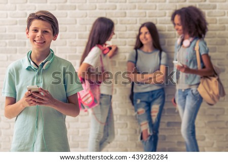 Teenage boy with headphones is using smartphone, looking at camera and smiling, three girls are talking in the background - stock photo