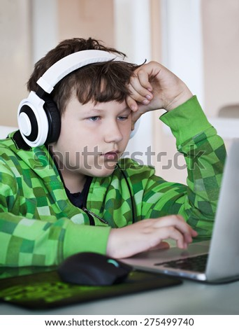 Teenage boy with headphones using laptop. - stock photo
