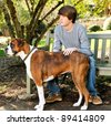 Teenage boy with his Boxer dog sitting on a park bench - stock photo