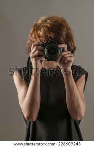 Teenage boy with punk dyed hair taking photograph
