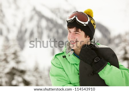 Teenage Boy With Snowboard On Ski Holiday In Mountains - stock photo