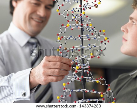 Teenage boy with teacher examining DNA model in science class - stock photo