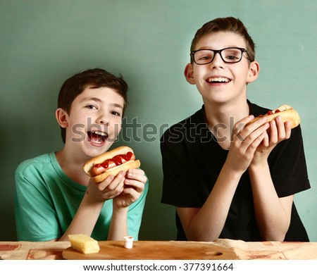 teenage boys cook hot dog happy close up smiling laughing portrait - stock photo