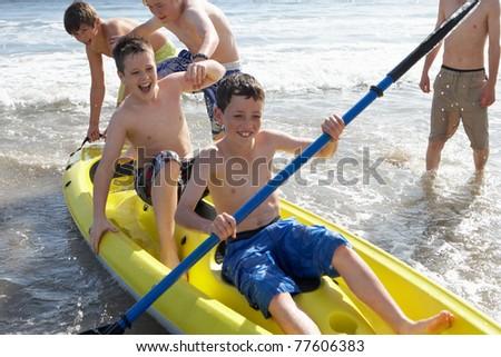 Teenage boys kayaking - stock photo