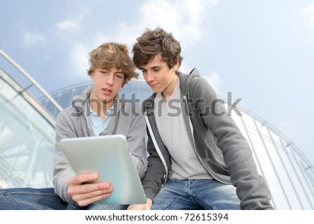 Teenage boys sitting outside with electronic tablet - stock photo
