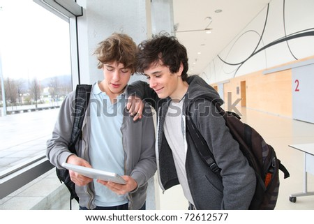 Teenage boys using electronic tablet in school hall - stock photo