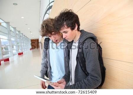 Teenage boys using electronic tablet in school hall - stock photo