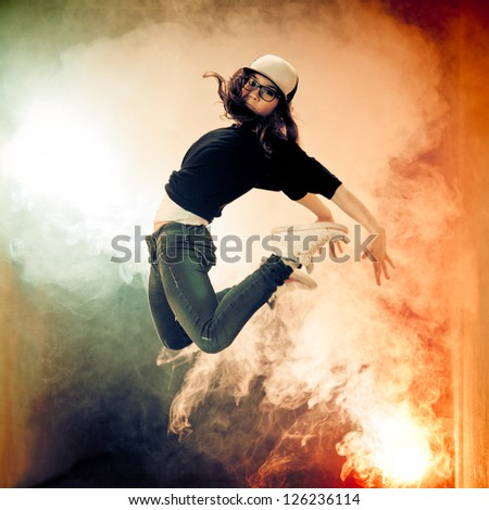 Teenage brakedancer girl jumping in a smoke - stock photo