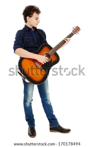 Teenage caucasian boy playing an acoustic guitar - stock photo