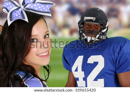 Teenage cheerleader with a football player on the field - stock photo