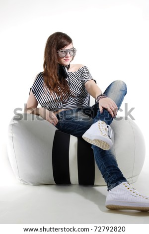 Teenage chick sitting with headphones on her neck