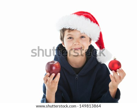 Teenage Christmas Boy looking happy straight into the camera. He is holding a red organic apple in his right hand and a red Christmas ball in his left hand.  - stock photo