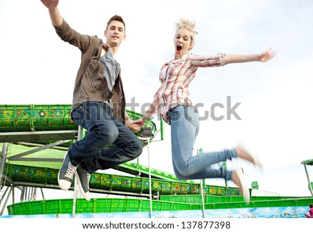 Teenage couple holding hands and jumping up in the air next to an attractions ride in an amusement park arcade during a sunny day. - stock photo