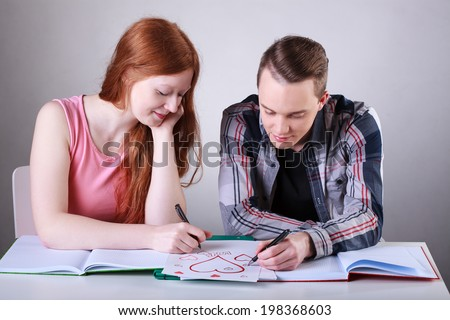 Teenage couple in love drawing hearts instead of learning