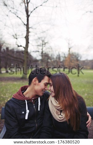 Teenage couple sitting on a bench and enjoying a day in the park. Beautiful young couple in park. Mixed race male and female model in love with copy space. - stock photo