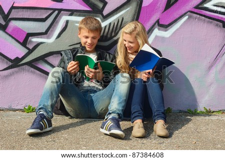 teenage couple studying in the park - stock photo