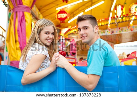 Teenage couple visiting a fun fair amusement arcade, sitting near a colorful ride with lights, holding hands and smiling. - stock photo