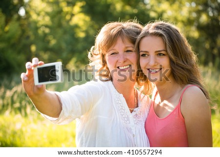 Teenage daughter and her senior mother are taking selfie photo with mobile phone - stock photo