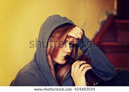 Teenage depressed woman sitting on the staircase and drinking a beer - stock photo