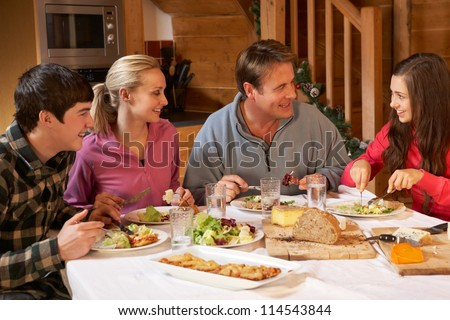 Teenage Family Enjoying Meal In Alpine Chalet Together - stock photo