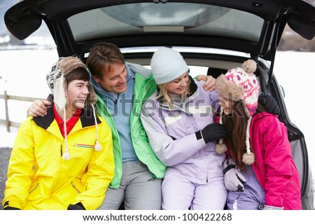 Teenage Family Sitting In Boot Of Car Wearing Winter Clothes - stock photo