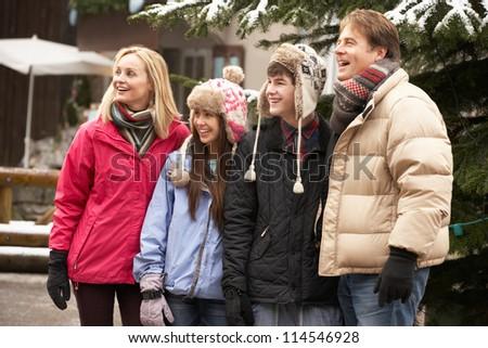 Teenage Family Walking Along Snowy Town Street In Ski Resort - stock photo