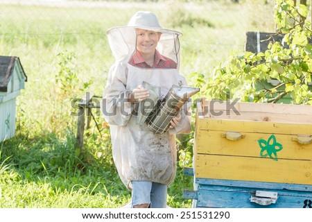 Teenage farm beekeeper checking hives on a bee yard - stock photo
