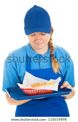 Teenage fast food worker disgusted by the burger and fries she's serving.  Isolated on white. - stock photo