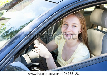 Teenage female driving student learning to drive a car - stock photo