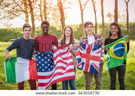 Teenage Friends Holding Flags from different Countries - stock photo