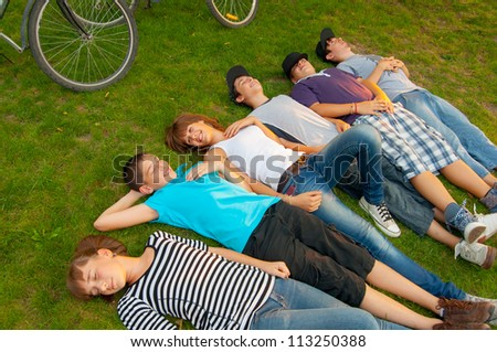 Teenage friends lying on the grass after riding bicycles. - stock photo