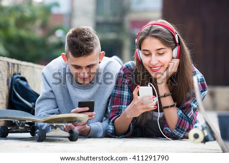 Teenage friends relaxing with mobile phones in sunny day outdoors - stock photo