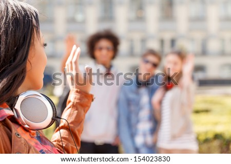 Teenage friends. Teenage girl looking at her friend s and gesturing while standing outdoors - stock photo