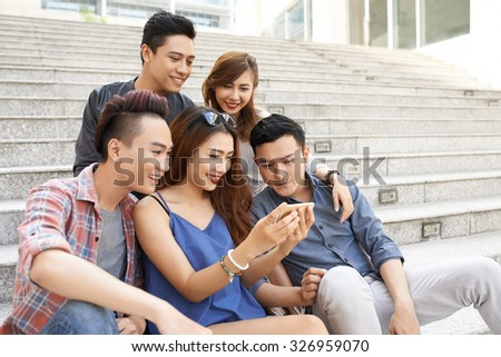 Teenage friends watching photos on smartphone together - stock photo